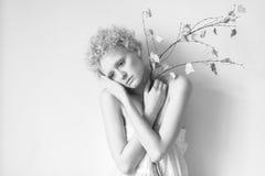 Mooi dun met het krullende model van het haarmeisje met een droge boomtak in de Studio Royalty-vrije Stock Fotografie