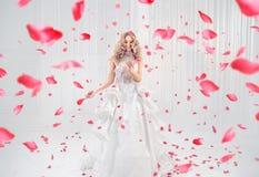 Mooi, elegant blonde die onder roze bloemblaadjes dansen Stock Afbeelding