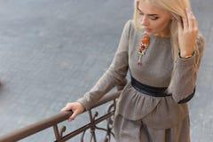 Mooi elegant slank blondemeisje in elegante kleding met broche omhoog de treden in de stad royalty-vrije stock foto's