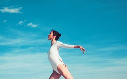 Mooi en bevallig Leuke balletdanser Jonge ballerina die op blauwe hemel dansen Mooi meisje in dansslijtage practicing royalty-vrije stock afbeelding