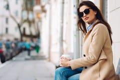 Mooi en jong meisje in een laag en een sjaal en zonnebril die op de bank zitten Vrouw het drinken koffie De zomer Royalty-vrije Stock Foto's