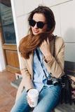 Mooi en jong meisje in een laag en een sjaal en zonnebril die op de bank zitten Vrouw het drinken koffie De zomer Royalty-vrije Stock Afbeelding