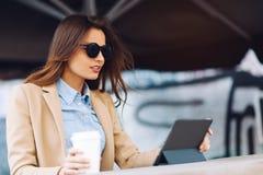 Mooi en jong meisje in zonnebril die koffie in de straat drinken en het nieuws in een tablet lezen Stock Fotografie
