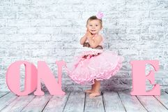 Mooi en leuk meisje in een roze kleding met brieven één op haar eerste verjaardag Emotioneel meisje stock foto