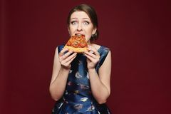 Mooi en modieus donkerbruin modelmeisje die in blauwe kleding pizza eten, dat bij wijnachtergrond wordt geïsoleerd, binnen stock foto
