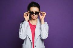 Mooi en modieus donkerbruin modelmeisje in rode kleding en laag die haar zonnebril aanpassen en bij violette achtergrond stellen Stock Afbeeldingen