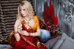 Mooi en sensueel blondemeisje in Indische rode saree op bac stock foto