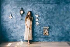 Mooi feemeisje die zich op blauwe achtergrond bevinden Stock Foto's
