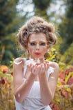 Mooi feemeisje in een bos die een kus geven Royalty-vrije Stock Afbeelding