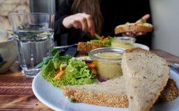 Mooi gedeelte van hummus en salade stock afbeelding