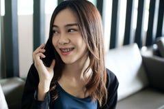 Mooi gelukkig glimlachend Aziatische onderneemster in kostuumjasje die smartphone, bedrijfsconcept met behulp van royalty-vrije stock fotografie