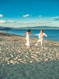 Mooi gelukkig mooi huwelijkspaar van de jonge handen die van de paopleholding zich bij water van oceaanstrand kust en het dansen  stock fotografie