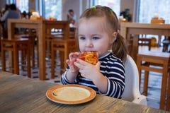 Mooi gelukkig jong meisje die grote plak van verse gemaakte pizza afbijten Zij zit bij witte stoel in koffie en geniet van yummy  royalty-vrije stock foto's