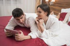 Mooi gelukkig jong paar die in bed na kuuroord genieten van Paar I stock fotografie