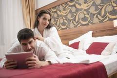 Mooi gelukkig jong paar die in bed na kuuroord genieten van Paar I stock foto's