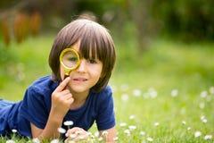 Mooi gelukkig kind, jongen, die aard met het overdrijven gla onderzoeken Stock Fotografie