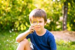 Mooi gelukkig kind, jongen, die aard met het overdrijven gla onderzoeken Stock Afbeeldingen