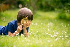 Mooi gelukkig kind, jongen, die aard met het overdrijven gla onderzoeken Stock Foto