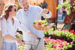 Mooi gelukkig medio volwassen paar die van kruidenierswinkel het winkelen terugkeren stock fotografie