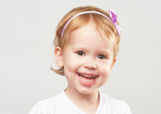 Mooi gelukkig meisje die en op een grijze achtergrond lachen glimlachen Stock Foto's
