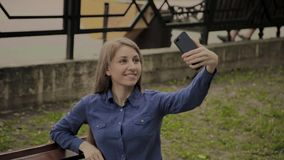 Mooi gelukkig meisje die selfie in het park op een bank maken stock video