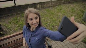 Mooi gelukkig meisje die selfie in het park op een bank maken stock videobeelden
