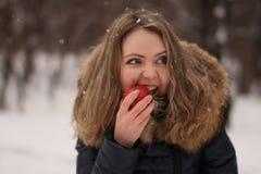 Mooi gelukkig meisje met lang krullend haar met een appel in haar handen Royalty-vrije Stock Fotografie