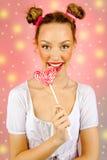 Mooi gelukkig meisje met sproeten die en de lolly van het snoepjessuikergoed met gelaatsuitdrukking houden eten Royalty-vrije Stock Fotografie