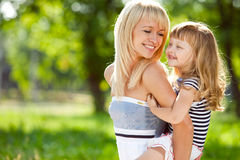 Mooi gelukkig meisje op de rug van haar moeder royalty-vrije stock afbeeldingen