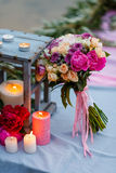 Mooi, gevoelig bruids boeket onder decoratie met kaarsen en verse bloemen Stock Afbeelding