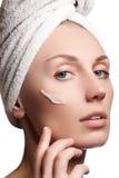 Mooi gezicht van jonge vrouw met kosmetische room op een wang De zorgconcept van de huid Close-upportret op wit wordt geïsoleerd  Stock Afbeeldingen