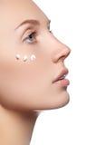 Mooi gezicht van jonge vrouw met kosmetische room op een wang De zorgconcept van de huid Close-upportret op wit wordt geïsoleerd  Stock Afbeelding
