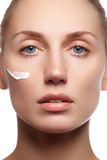 Mooi gezicht van jonge vrouw met kosmetische room op een wang De zorgconcept van de huid Close-upportret op wit wordt geïsoleerd  Stock Foto