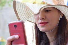 Mooi Gezicht van middenleeftijdsvrouw die Zondaghoed dragen die Internet met smartphone doorbladeren stock foto