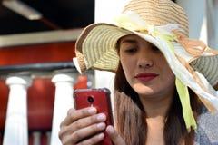 Mooi Gezicht van middenleeftijdsvrouw die Zondaghoed dragen die Internet met smartphone doorbladeren royalty-vrije stock foto's