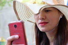 Mooi Gezicht van middenleeftijdsvrouw die Zondaghoed dragen die Internet met smartphone het glimlachen doorbladeren royalty-vrije stock afbeelding