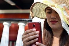 Mooi Gezicht van middenleeftijdsvrouw die Zondaghoed dragen die Internet met smartphone het glimlachen doorbladeren stock fotografie