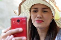 Mooi Gezicht van middenleeftijdsvrouw die Zondaghoed dragen die Internet met smartphone het glimlachen doorbladeren royalty-vrije stock fotografie