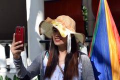 Mooi Gezicht van middenleeftijdsvrouw die Zondaghoed dragen die Internet met smartphone het glimlachen doorbladeren royalty-vrije stock afbeeldingen