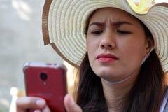 Mooi Gezicht van middenleeftijdsvrouw die Zondaghoed dragen die Internet met smartphonefrowns doorbladeren stock foto's