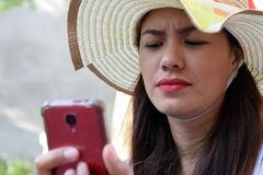 Mooi Gezicht van middenleeftijdsvrouw die Zondaghoed dragen die Internet met smartphonefrowns doorbladeren stock foto