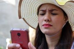 Mooi Gezicht van middenleeftijdsvrouw die Zondaghoed dragen die Internet met smartphonefrowns doorbladeren royalty-vrije stock fotografie