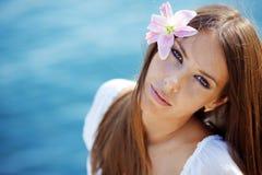 Mooi gezicht van vrouw met lelie in haar haar Stock Fotografie