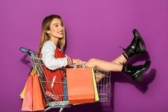 mooi glimlachend Aziatisch meisje die met document zakken in het winkelen karretje zitten en weg het kijken royalty-vrije stock afbeeldingen