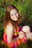 Mooi glimlachend gembermeisje die met gesloten ogen op gras zitten stock foto's