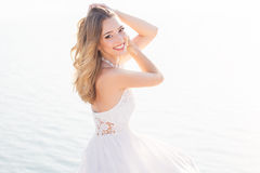 Mooi glimlachend jong bruidmeisje over het overzees royalty-vrije stock afbeelding
