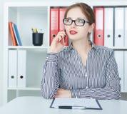 Mooi glimlachend jong meisje die op de mobiele telefoon in het bureau spreken Royalty-vrije Stock Foto