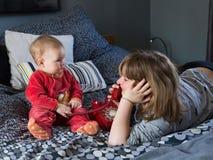 Mooi glimlachend meisje die bij bed het spelen met uitstekende rode telefoon en haar leuke mollige babyzuster liggen royalty-vrije stock fotografie