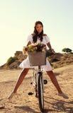 Mooi glimlachend meisje die een fiets langs de overzeese kust berijden Stock Foto