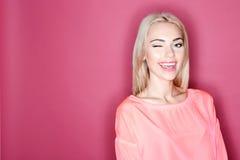 Mooi glimlachend meisje die op roze achtergrond knipogen Stock Afbeeldingen